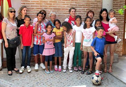 Los 8 niños saharauis con sus familias de acogida posan en el Patio de Columnas del Ayuntamiento.