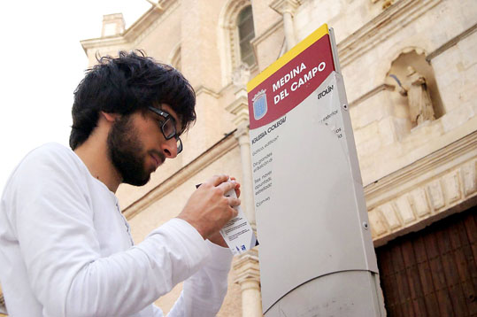 El estudiante medinense de ingeniería informática Adrián de la Rosa, promotor del proyecto, coloca un código QR en el cartel informativo de la Colegiata de San Antolín.
