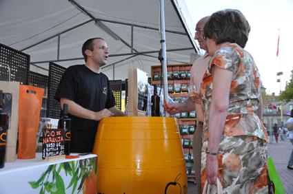 Un productor de vino ecológico departe con una pareja de clientes.