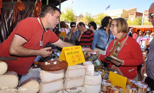 Un artesano alimentario ofrece sus quesos a una clienta en la Feria de Productos de la Tierra.