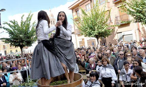 Dos jóvenes realizan el tradicional pisado de la uva en la Fiesta de la Vendimia de Rueda.