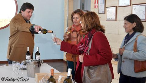 El guía de la bodega 'Reina de Castilla' de La Seca ofrece vino a un grupo de visitantes.