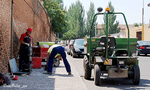 Dos operarios arreglan un desperfecto en el pavimento junto a la tapia del Hospital Simón Ruiz.